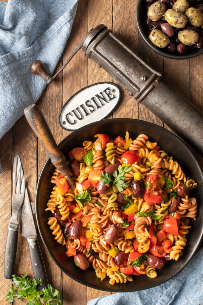 simple italian pasta salad in black bowl next to spice grinder and bowl of olives