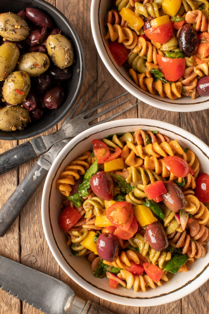 simple italian pasta salad in small white bowls next to bowl of olives