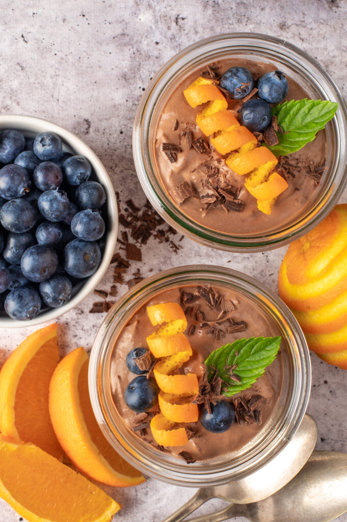 creamy chocolate coconut pudding in jars next to blueberry in dish