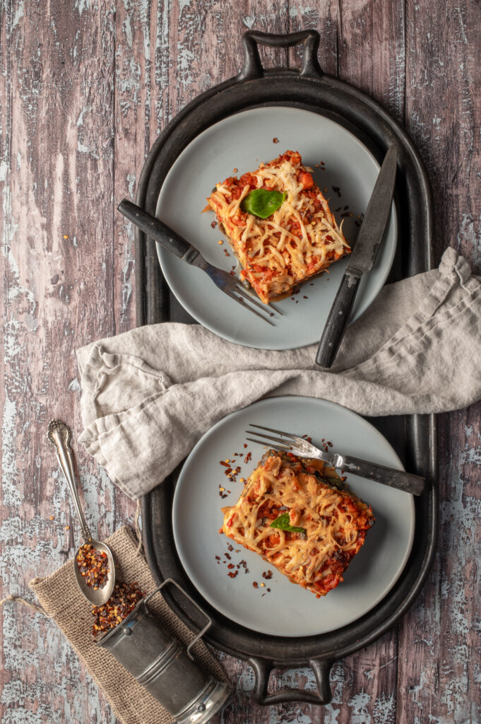 lasagne on two plates sitting on cast iron griddle