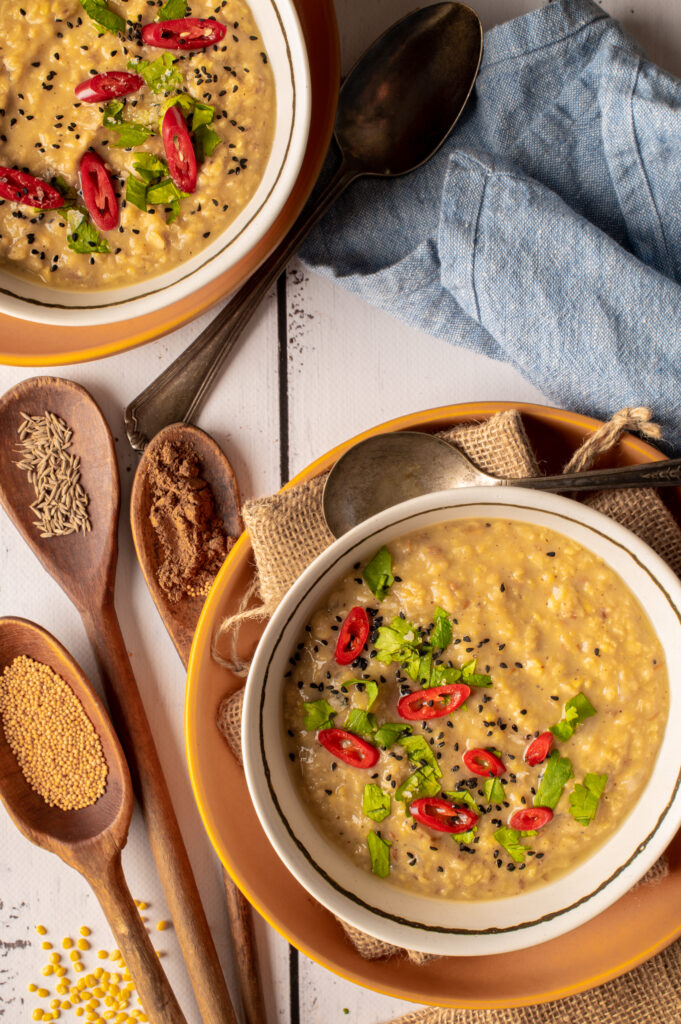 basic mung dal in two white bowls next to spices in wooden spoons