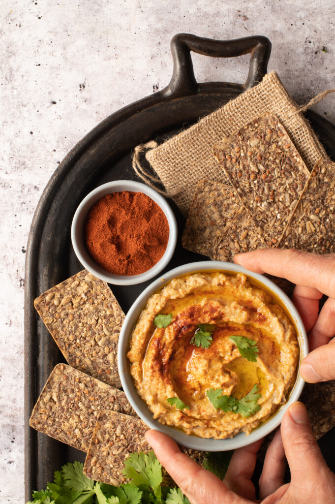 baba ganoush in bowl on iron serving plate with crackers