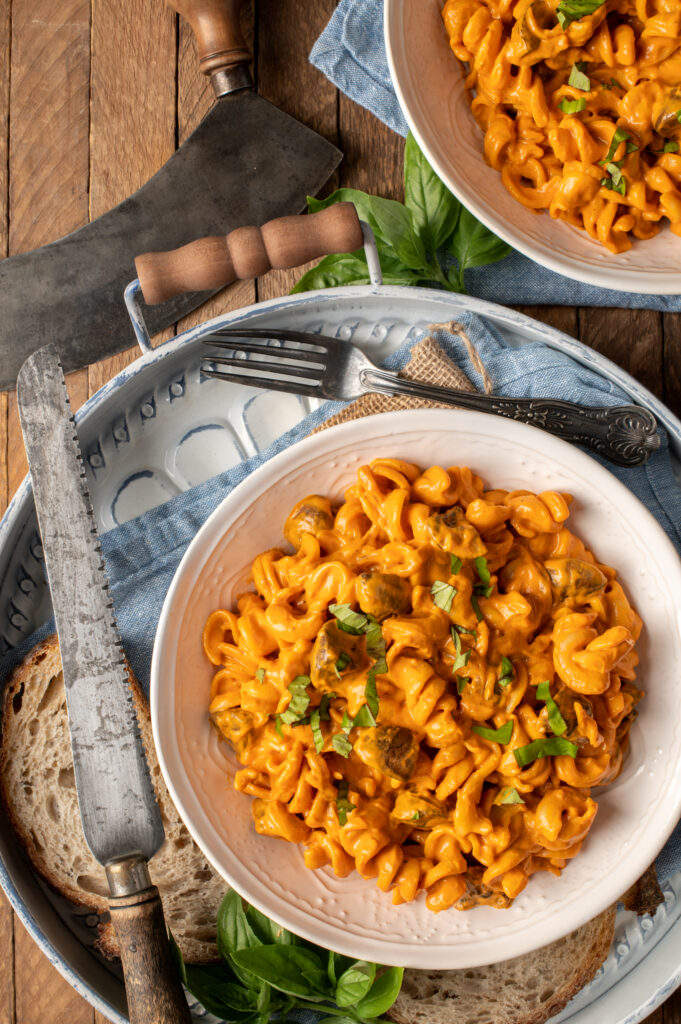 creamy roasted red pepper pasta in white bowl on tray