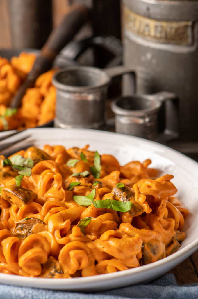 creamy roasted red pepper pasta in white bowl with measuring cups in background