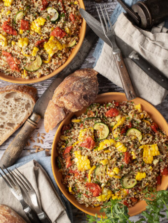 quinoa with summer vegetables on two plates next to cutlery an sourdough slices