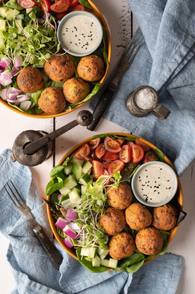 two falafel plates with tomatoes, cucumber and greens
