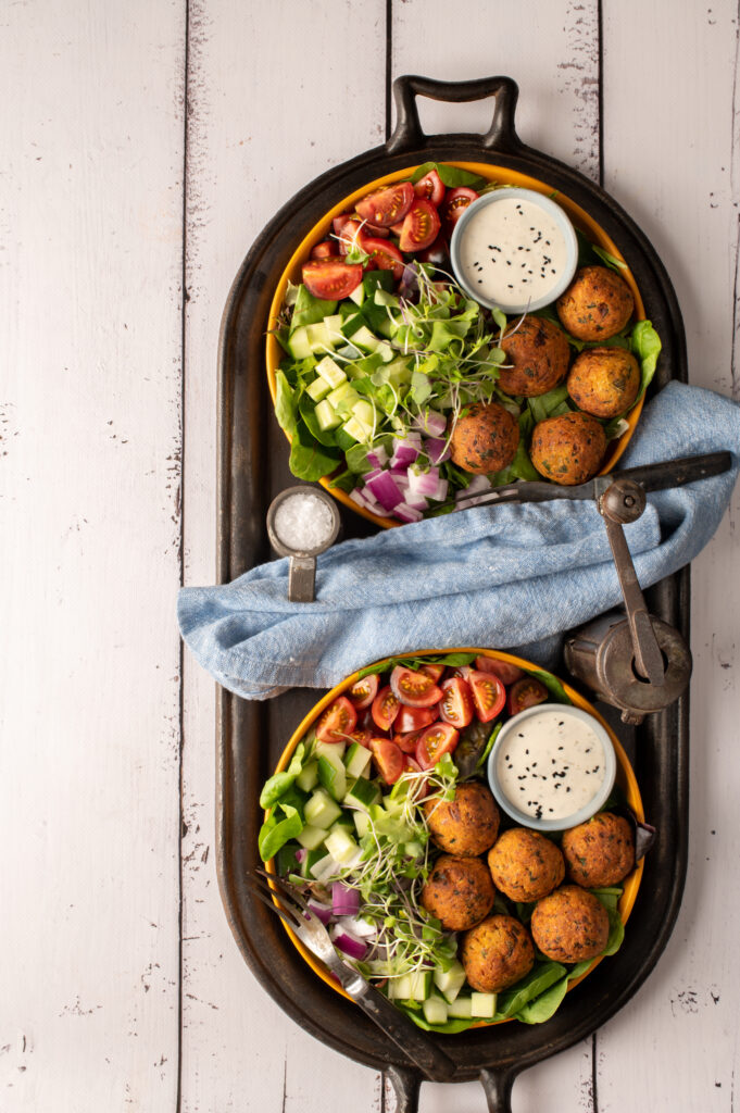 two falafel plates with tomatoes, cucumber and greens sitting on iron griddle